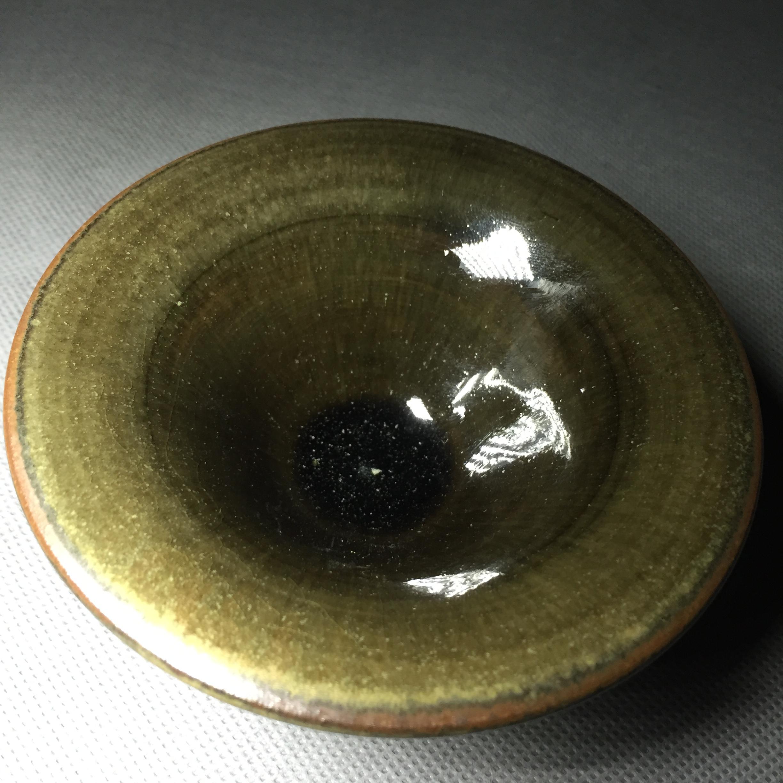 茶末绿釉撇口盏,釉底的白晶稀疏地洒成一片