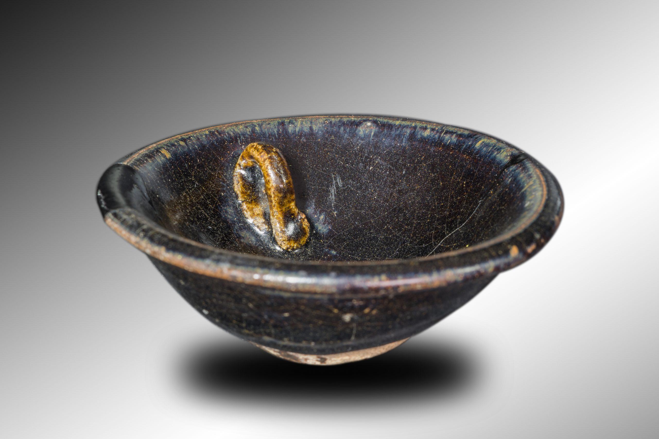 釉面黝黑盏内有一个小耳用于支撑灯芯的乌金釉灯盏